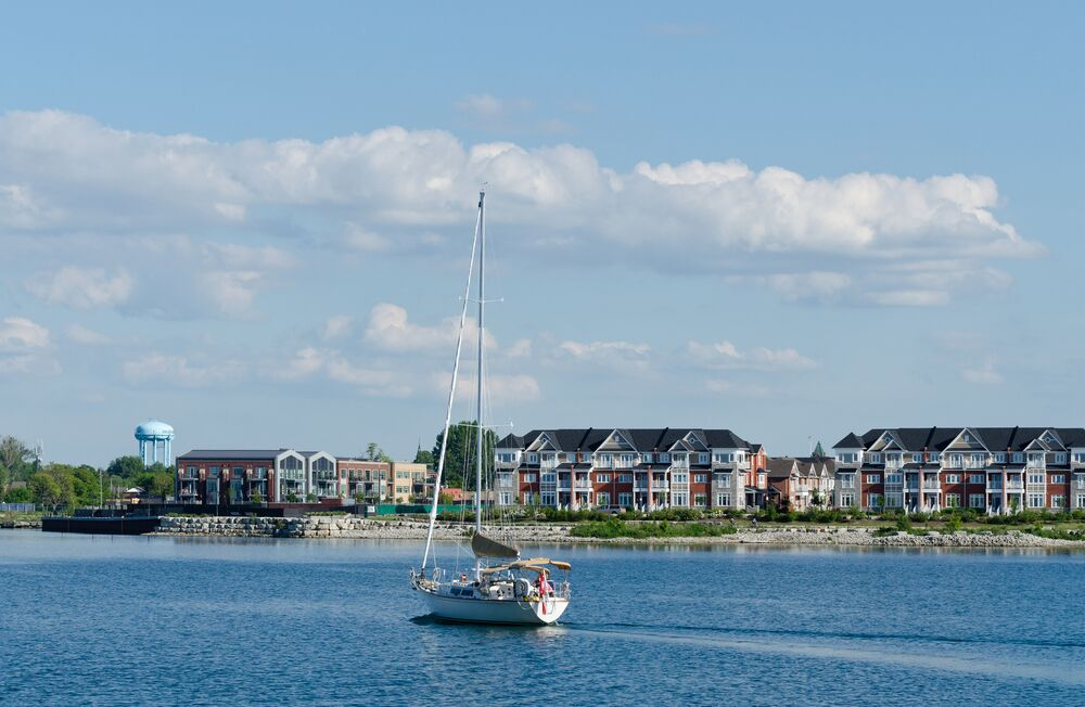 Sailboat on the water with homes in the back